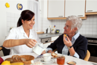 caregiver preparing meal for her patient